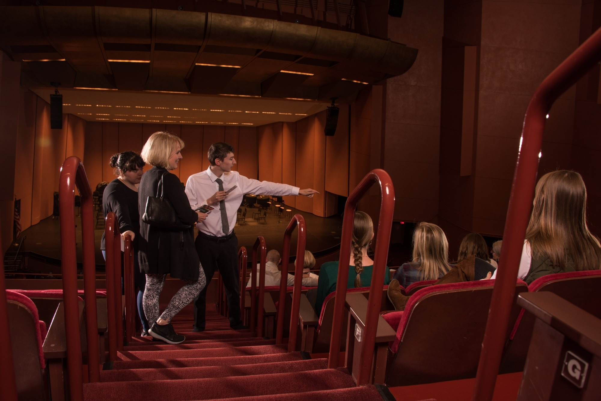 Image of an usher in a white shirt and black tie pointing guests toward their seats at the Lied Center