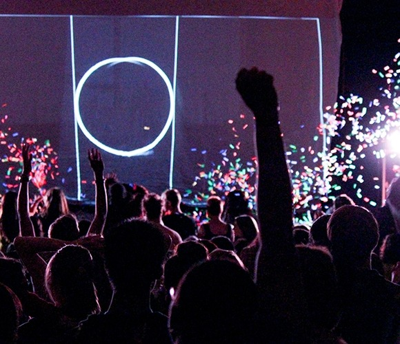 Image from the back of the hall toward the stage showing UNL students in the audience with hands raised and confetti flying in the air during a free Ok Go concert at the Lied Center