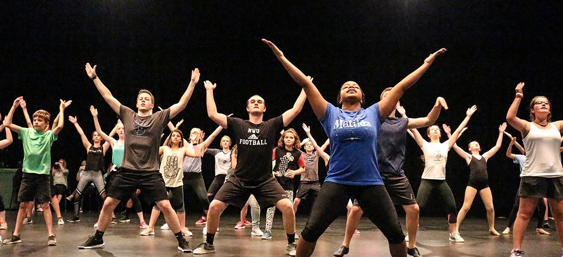 Image of students led by a Matilda performer holding their arms spread apart above their heads during a dance master class