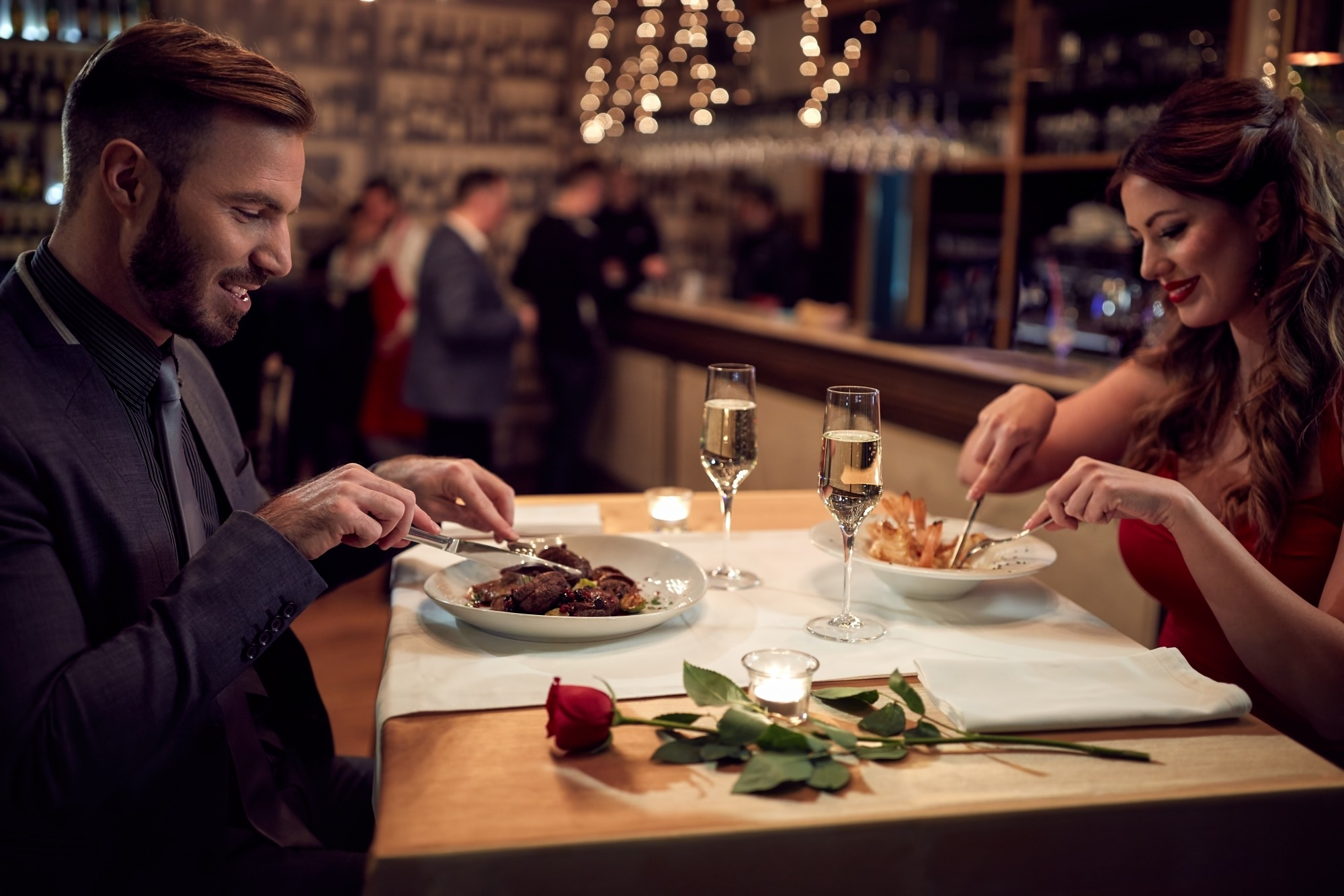 image of couple dining at restaurant with wine and a red rose on the table.