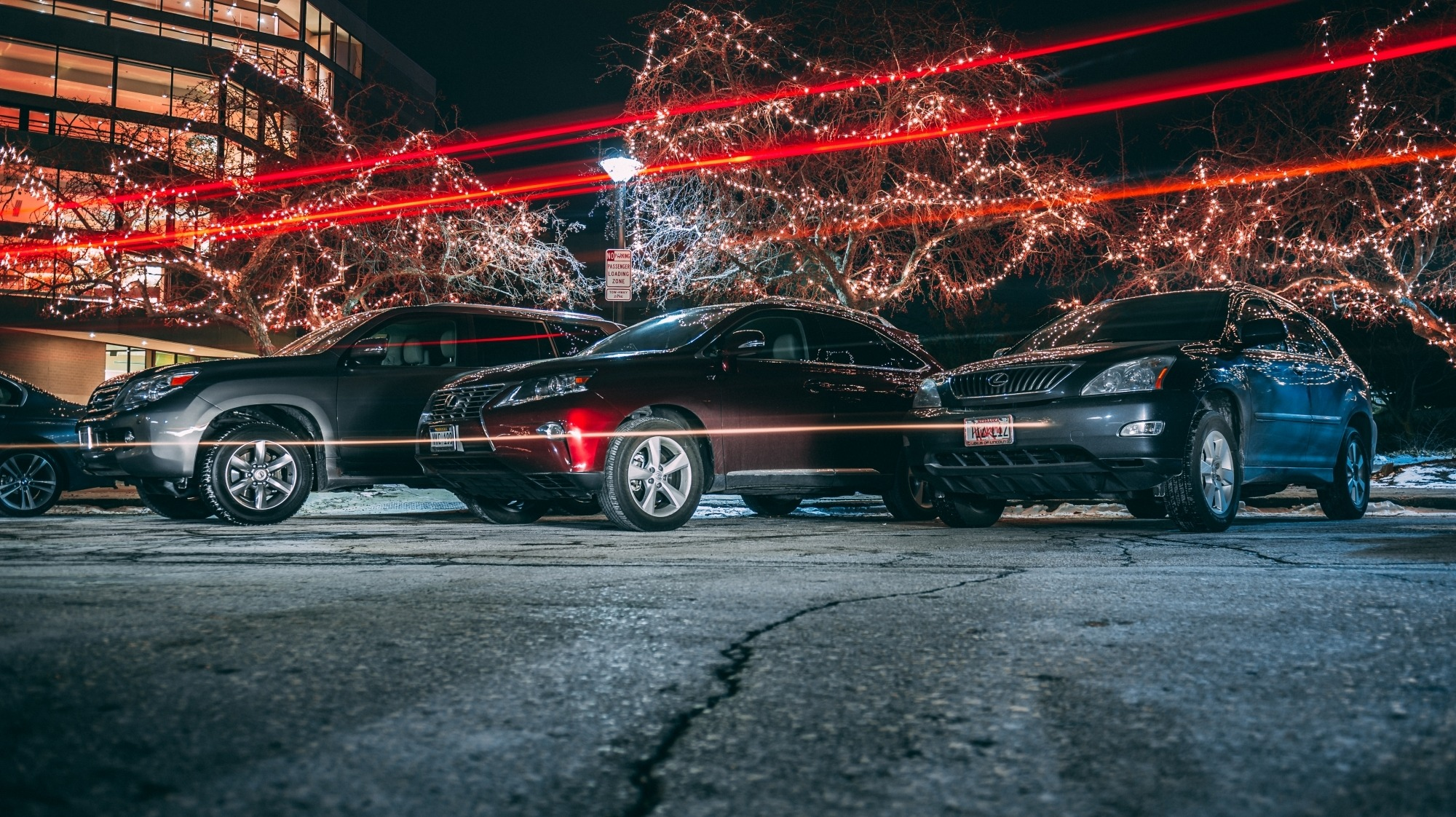 Image taken from a low angle of three vehicles parked at night in front of the Lied Center with lights streaking across the picture