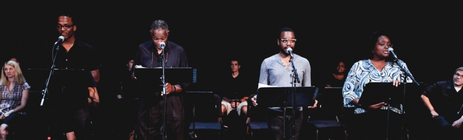 Image of four performers standing in front of microphones and music stands with an audience seated behind them against a black background for the ASCAP Grow A Show staged reading in the Lied Center Johnny Carson Theater.