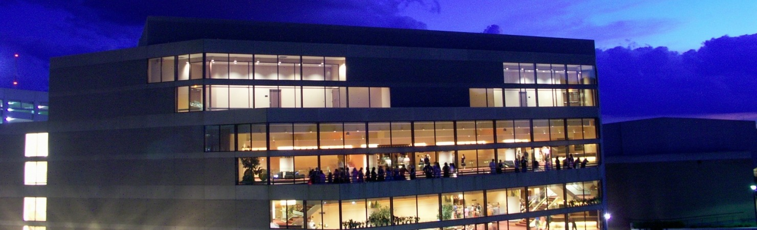 Image of the Lied Center building taken from the roof of a nearby building at dusk with a brilliant blue sky.