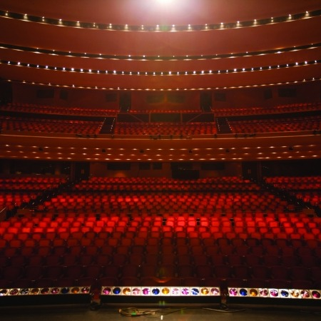 Image of the Lied Center auditorium taken from the stage looking out into an empty hall full of red, plush seats.