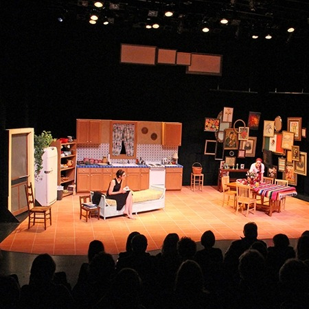 Image of a play hosted in the Lied Center Johnny Carson Theater featuring a set that looks like a living room and kitchen.