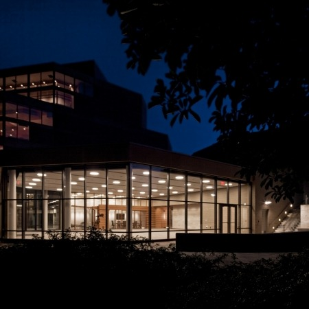 Image of the Lied Commons building taken outside at night looking in through the windows with the lights on at night