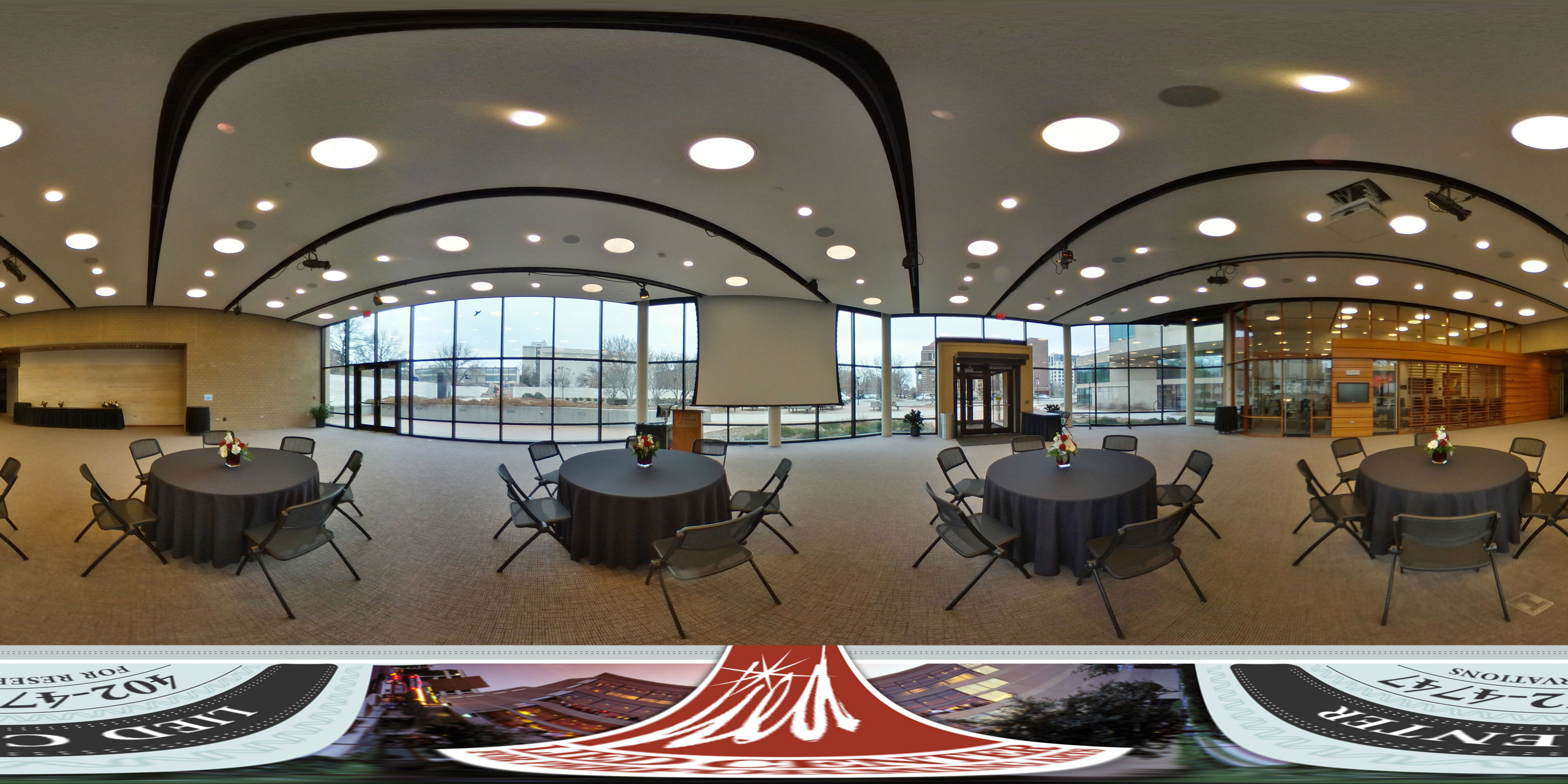 Virtual tour of the Lied Commons showing a banquet setup featuring round tables with black tablecloths and chairs and red and white flowers.